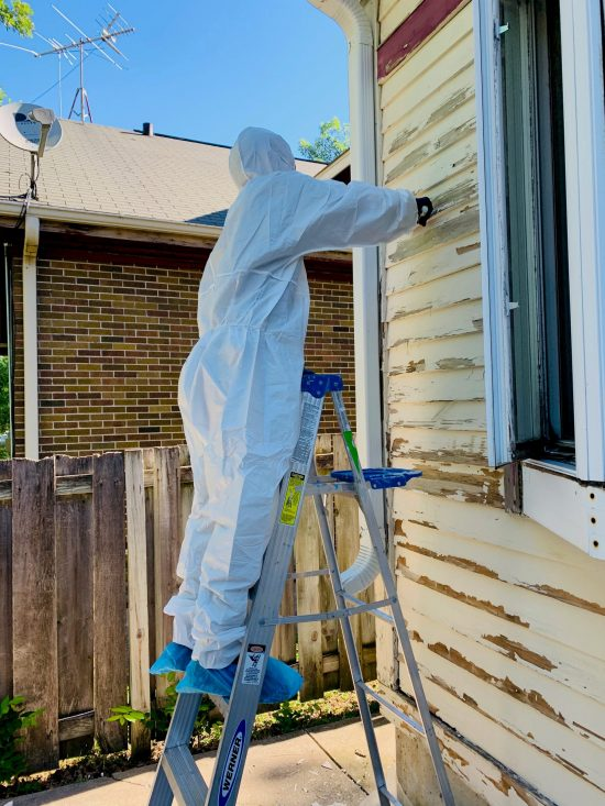 painter working on house with lead paint